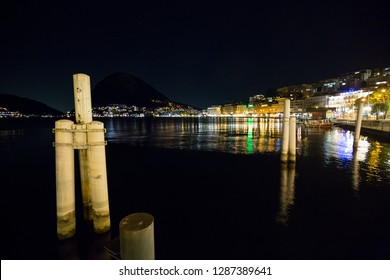 Lugano, Switzerland - 10 January 2019: Boulevard of Lugano near the lake with poles for the boats late in the evening