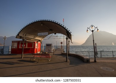 Lugano, Switzerland - 7 January 2019: The ferry terminal at the city centre of Lugano with lake and mountains at the background