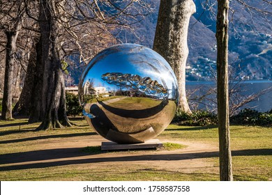 Lugano, Switzerland, Feb 2020, modern art - reflective metal ball - in the public park Parco Ciani