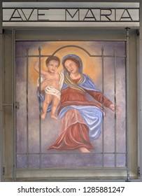 LUGANO, SWITZERLAND - JUNE 24, 2018: Virgin Mary with baby Jesus, house facade in Lugano, Switzerland