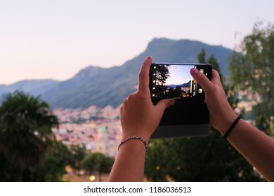 Lugano Switzerland - June 29, 2018: Beautiful medieval town Lugano on a phone, woman taking a picture of the skyline