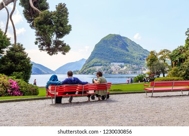 LUGANO, SWITZERLAND - MAY 12, 2018:These are unidentified people who rest on the benches of the city's Chiani Park with a beautiful view of Lake Lugano.