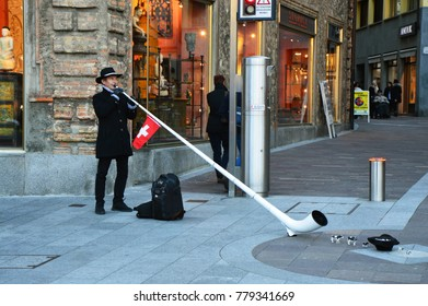 LUGANO, SWITZERLAND - NOVEMBER 27, 2017: Swiss musician with a typical Alphorn in Lugano city. A man in traditional Swiss costume playing the alphorn, Switzerland's traditional music instrument