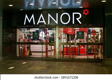 Lugano, Ticino, Switzerland - 5th January 2020 : Manor department store entrance at night in Lugano. Manor is the largest department store chain in Switzerland