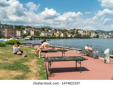 Lugano, Ticino, Switzerland - August 5, 2019: People enjoying Lugano Lake promenade in a hot summer day in the center of Lugano, Switzerland