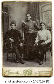 LUGANSK,RUSSIAN EMPIRE - CIRCA 1900s: Studio portrait of young woman and two men, photo studio by S. Umansky, Lugansk, Ukraine, 1900s