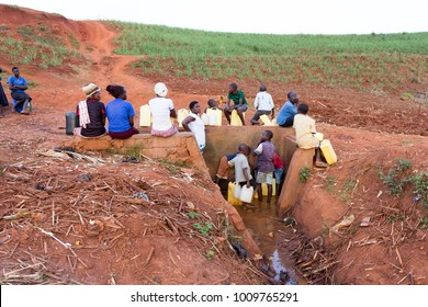 Lugazi, Uganda. 13 June 2017. A group of Ugandan people - men, women, children - filling jerrycans with water in a local water well.
