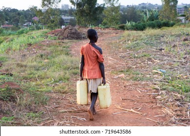 Lugazi, Uganda. 13 June 2017. A young girl heading off carrying jerrycans full of water. She is dressed in rags.