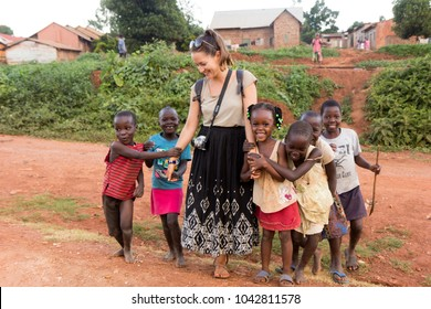 Lugazi, Uganda. 17 May 2017. A white-skinned volunteer (called 'mzungu' or 'muzungu' by the locals) holding hands with Ugandan children in a rural area.