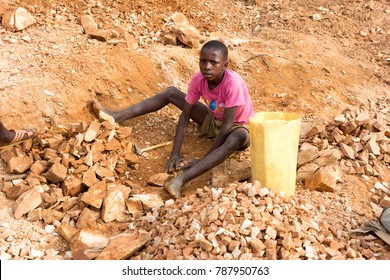 Lugazi, Uganda. June 18 2017. A Ugandan boy breaking rocks into small slabs for his foreman. Basically child labour.