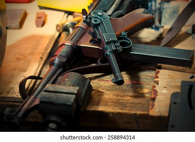 Luger pistol and mashinegun MP 38 in gunsmith on old wooden surface. instagram image retro style