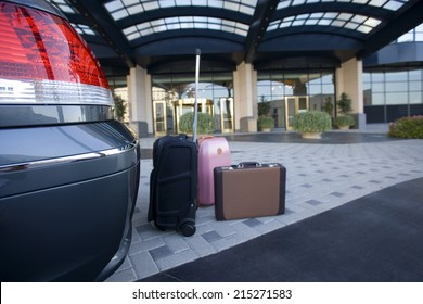 Luggage beside parked car outside hotel