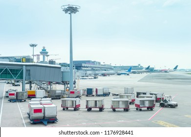 Luggage carriages by gangway at Changi airport terminal with airplanes, Singapore