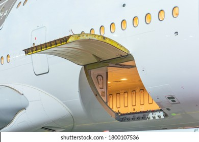 Luggage compartment with open door in wide-body long-haul aircraft.
