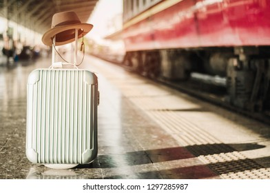 Luggage and hat  are placed on platform in the train station, while awaiting trains with abstract concepts, learning and travel to a wide world of travelers (vintage style)