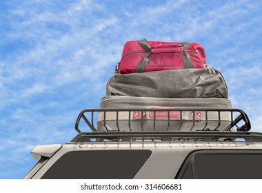 Luggage on van roof rack. Cloth suitcase and duffle bags on top of minivan metal carrier. Blue sky and clouds background.