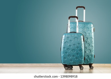 Luggage policy. Two green suitcases isolated on green background. Check-in suitcase and carry-on bag. Copy space. Studio shot.