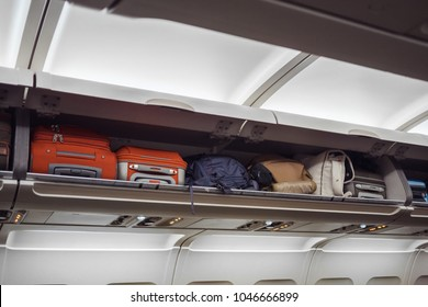 Luggage shelf with luggage in an airplane. Aircraft interior. Travel concept.