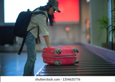 Luggage in transfer belt of the airport terminal being takes or bring by hand of woman traveler to keep away in arrival hall of the airport, traveling to destination concept