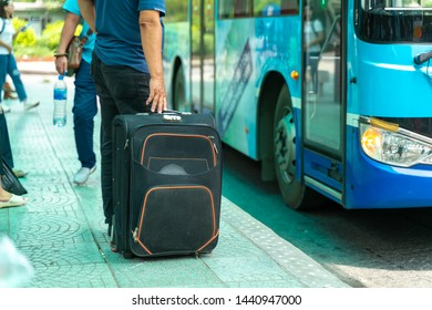 Luggage of a traveller at bus stop with the bus on background