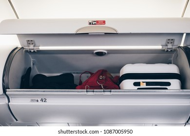 Luggages in the airplane overhead bin.