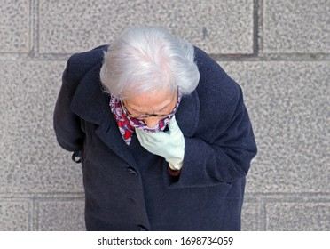 Lugo, Spain. 05/04/2020. Senior caucasian woman with white hair covers her mouth. Elderly mature woman walking on the streets during quarantine. Ancient people are considered population at risk.