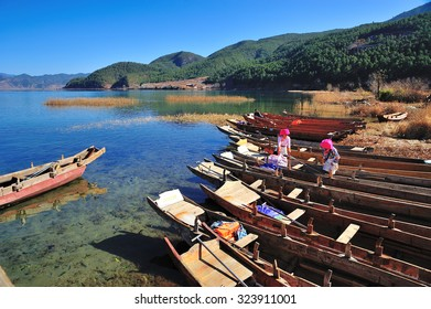Lugu Lake, China â?? Dec 30 2013: Local Boat owner cleaning their boat.