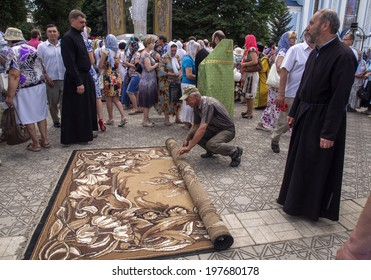 LUHANSK, UKRAINE - June 9, 2014:  Verger turns carpet at the end of the prayer. Archbishop Luhansk and Alchevsk Mytrofan held prayer for peace in the city center. Hundreds of faithful prayed with him.
