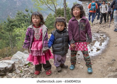 LUKLA, KHUMBU REGION, NEPAL - APRIL 24, 2017: Three cute young nepalese girls standing on a trekking trail in Lukla village, Khumbu region, Himalaya, Nepal on 24 April, 2017.