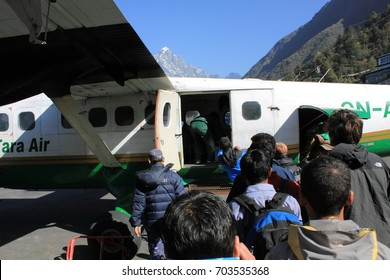 Lukla / Nepal - April, 2012: terkkers and Locals boarding small aircraft at Lukla Airport, a small dangerous airstrip considered to be the gate to Everest Region.