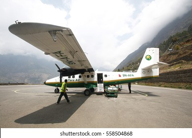 LUKLA, NEPAL - MAY 3, 2014: Unidenified ground crew unloading luggage from Tara air plane at Tenzingâ??Hillary Airport, a small airport in the town of Lukla, in Khumbu, Solukhumbu District, Nepal