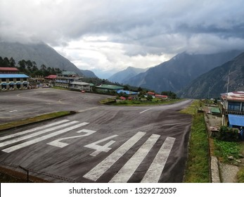 LUKLA, SOLUKHUMBU DISTRICT, NEPAL - OCTOBER 31, 2015: Tenzing–Hillary Airport runway, Himalayan mountains in haze in the background, gates to Everest, eastern Nepal