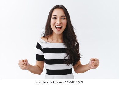 Luky, enthusiastic good-looking east-asian brunette girl motivated, determined win, clench fists empowered, smiling thrilled and joyful, feeling excited as watching thrilling game, white background