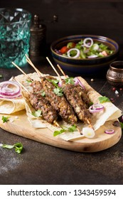Lula kebab from minced meat on pita bread (lavash), shish kebab. With red onion, cilantro and vegetable salad