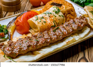 lula kebab spicy with vegetables in Turkish on the board