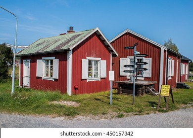 Lulea, Sweden - August 4, 2014: Houses at Gammelstad Lulea, Sweden. On a crossroad is a signpost with direction to the highlights of the park.