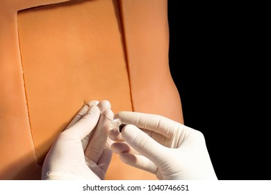 Lumbar puncture or epidural anesthesia  procedure technique on a simulation medical training model. Medical procedure concept, simulation medicine training. Doctor in gloves with a needle.