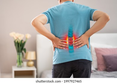 Lumbar spine hernia, man with back pain at home, compression injury of the intervertebral disc in the lower back, photo with highlighted skeleton