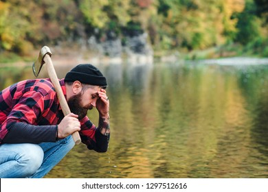 Lumberjack with an ax in his hands. Brutal bearded man. Bearded lumberjack. Brutal bearded man with beard and moustache by river near forest.