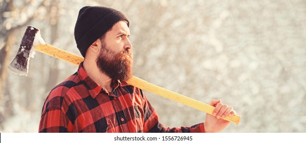Lumberjack with an ax in his hands. Male holds an ax on a shoulder. Brutal bearded man. Bearded lumberjack. Brutal bearded lumberjack with ax in winter forest. Handsome man, hipster in snowy forest.