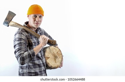 A lumberjack with an ax over his shoulder and a log under his arm. Logman with checkered shirt and an orange hat. Plenty of space for your own text / copy space.