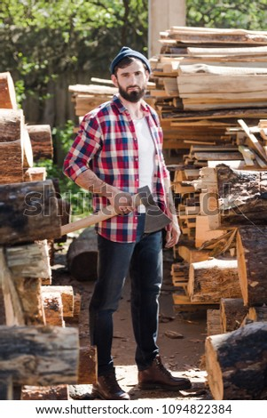 bd1ba8ab2dd lumberjack in checkered shirt standing with axe between logs at sawmill