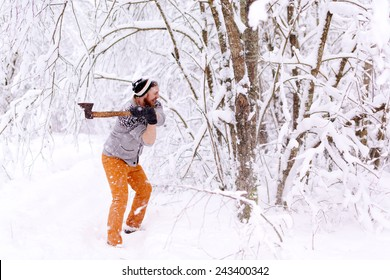 Lumberjack chopping wood. Bearded man with an ax chopping wood with snowy winter forest.
