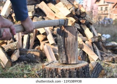 Lumberjack chopping wood for winter, Young man chopping woods with old ax