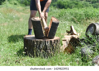 Lumberjack chopping wood for winter. Young man chopping woods with an axe