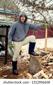 A lumberjack chops wood for a stove in a house for the cold season