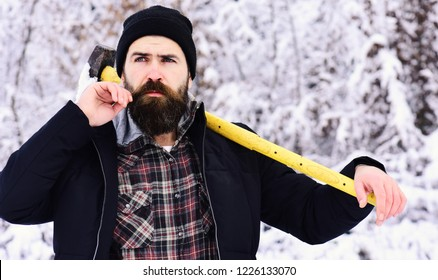 lumberjack concept. lumberjack man working in the winter forest. Guy with thoughtful face with forest covered by snow on background. Hipster woodsman concept. Man in hat with beard and mustache holds