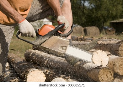 Lumberjack cutting the log of wood with petrol chainsaw