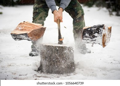 The lumberjack is cutting wood in snow while falling snow at winter.