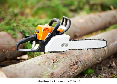 Lumberjack power Work tool petrol Chainsaw lying on log In The Forest